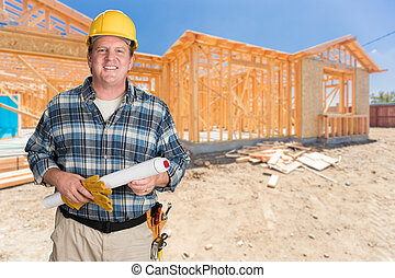 Male Contractor With House Plans Wearing Hard Hat In Front of New House Construction Framing