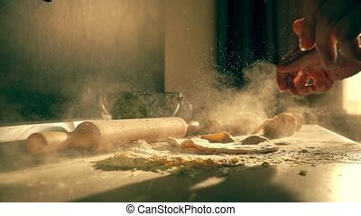 Male cook throwing homemade pasta dough on the table, super...
