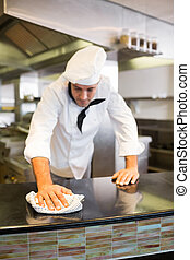 Male cook wiping kitchen counter - Male cook wiping the...
