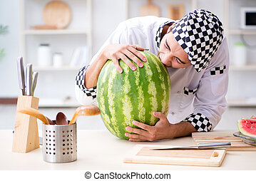 Male cook with watermelon in kitchen