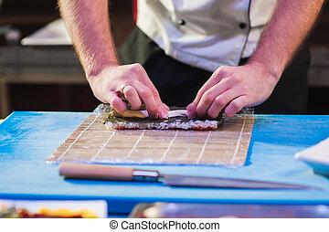 Male cooks preparing sushi