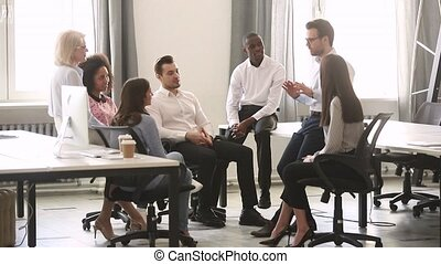 Male corporate team leader teaching diverse workers group at...