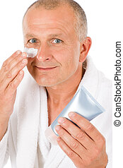 Male cosmetics - senior man apply facial cream