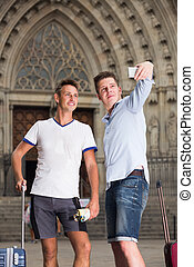 Male couple with luggage doing selfie picture at travel