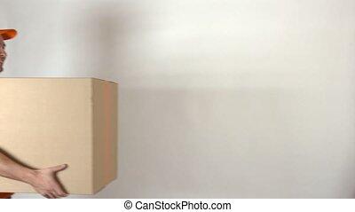 Male courier in orange uniform delivering big parcel. Grey backround, isolated. 4K video