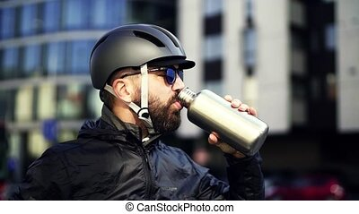 Male courier with sunglasses drinking water when delivering...