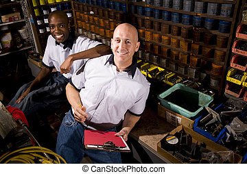 Male coworkers working in front of colored inks in print shop
