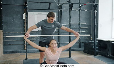 Male crossfit instructor teaching young woman holding metal ...