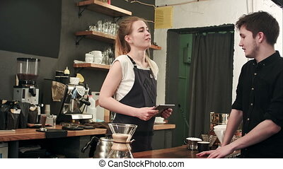 Male customer asking barista to make coffee in cafeteria....