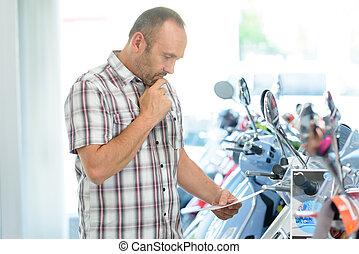 male customer browsing in motorcycle showroom