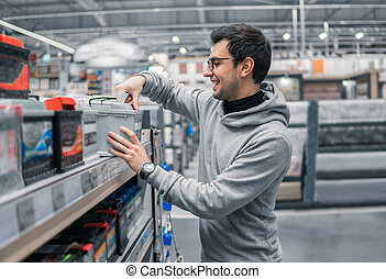 male customer buying car battery n the car supermarket