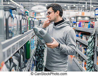 male customer buying engine lubricating oil in the car supermarket