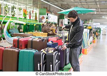 male customer choosing travel suitcase