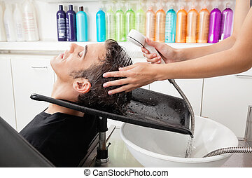 Male Customer Having Hair Washed At Salon - Side view of...