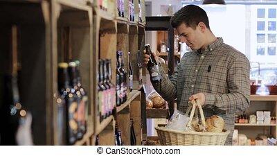Male Customer In Delicatessen Choosing Bottle Of Beer From...