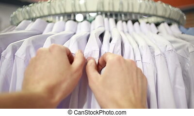 male customer looking for T-shirts in a fashion store