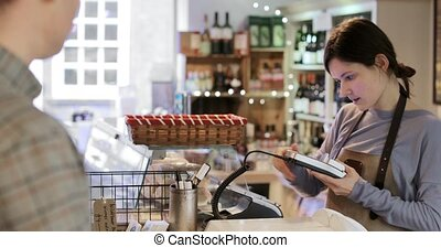 Male Customer Paying Sales Assistant For Shopping In Delicatessen With Contactless Credit Card