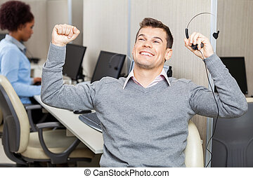 Male Customer Service Representative With Arms Raised...
