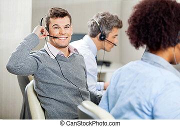 Male Customer Service Representative Using Headset In Office