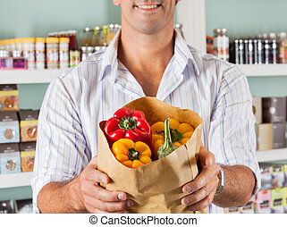 Male Customer Showing Bell peppers In Paper Bag