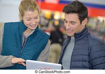 male customer showing digital tablet to female vendor