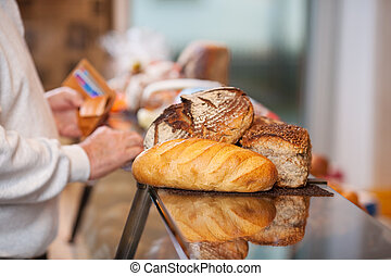 Male Customer With Breads Placed On Counter