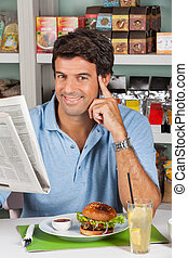 Male Customer With Snacks And Newspaper In Supermarket