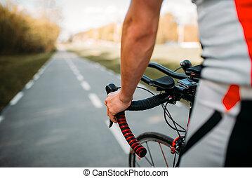 Male cyclist in sportswear cycling on asphalt road