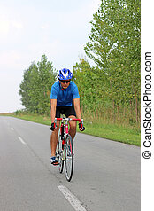 male cyclist riding a bike on an road