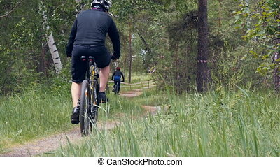 male cyclist riding woman Bicycle in woods