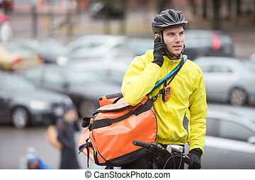 Male Cyclist With Courier Bag Using Mobile Phone On Street...