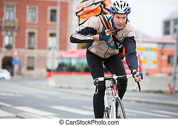 Male Cyclist With Courier Delivery Bag Riding Bicycle