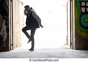 Male dancer freestyling in urban setting