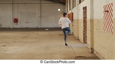Front view of a Caucasian male ballet dancer practicing in an empty warehouse, dancing and turning, slow motion. Cool Generation Z hipster style concept.