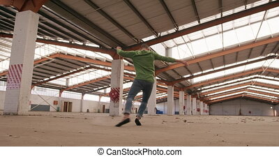 Male dancer in an empty warehouse - Side view of a Caucasian...