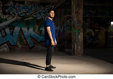 Male dancer in front of a graffiti wall