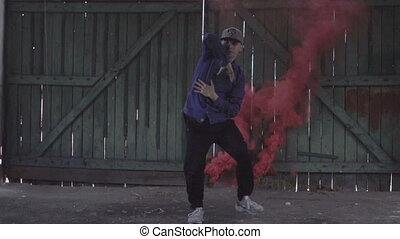 Male dancing freestyle in smoke. - Active young male dancing...