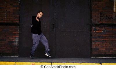 Male dancing on brick wall
