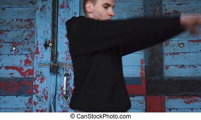 Male dancing over blue door