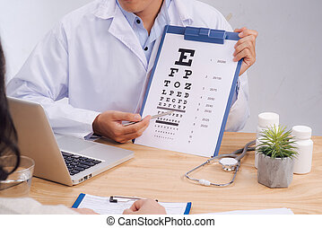 Male dcotor pointing at the letters on the eye chart for her patient to read