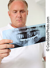 Male Dentist Analyzing Xray In Clinic - Low angle view of...