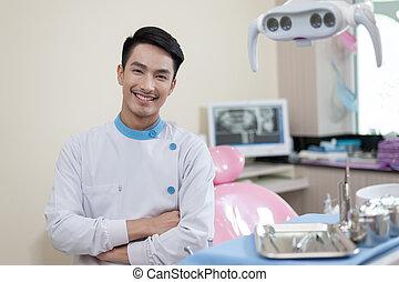 Male dentist crossing armin dental clinic - Male dentist...