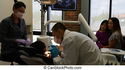 Male dentist examining a patient with tools 4k