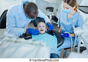 Male dentist examining patients teeth while nurse holding saliva ejector