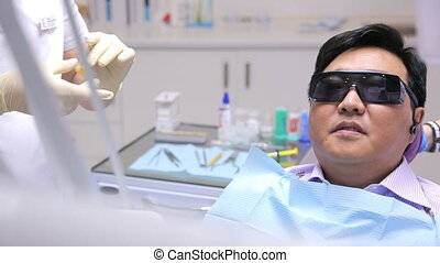 Male dentist makes a mold of front teeth of patient using yellow mass.