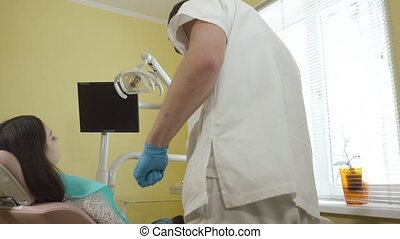 Male dentist prepares for the review a female patient in the...