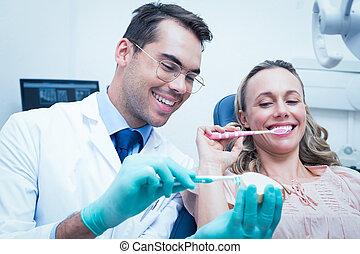 Male dentist teaching woman how to brush teeth
