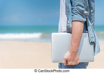 Male digital nomad hand holding laptop on the beach