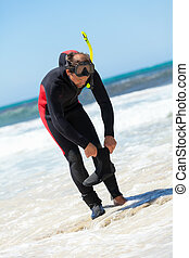 male diver with diving suit snorkel mask fins on the beach