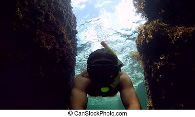 male dives with shooter camera in hand. - Young Diver...